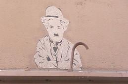 Charlie Chaplin sur un mur, qui picote du pain dur...