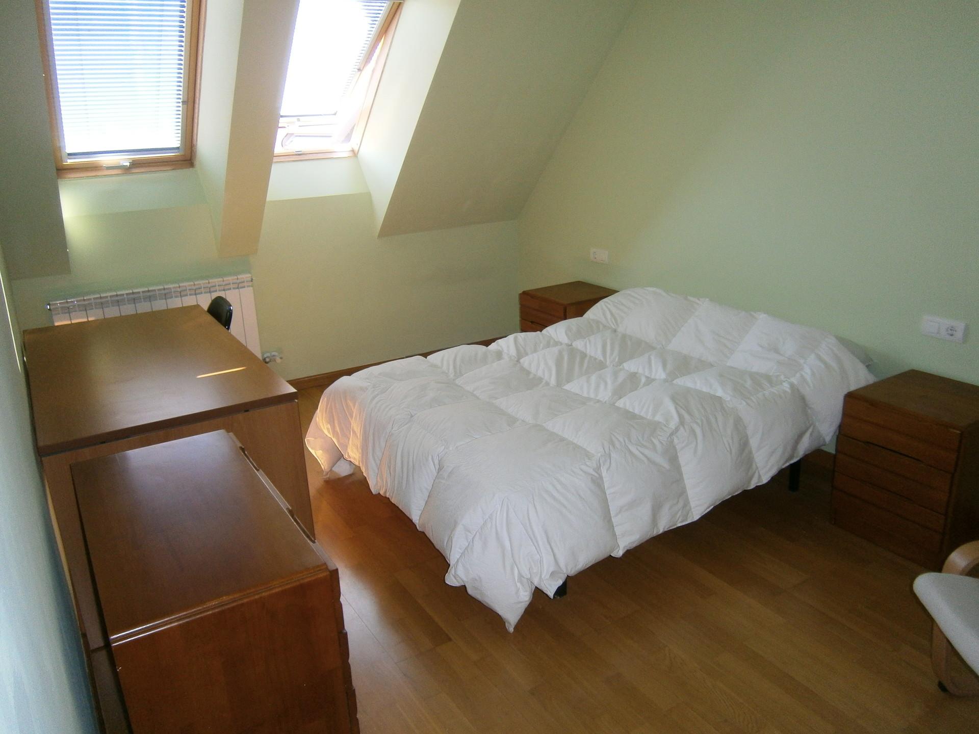 Habitación con cama doble y mesa de estudio grande