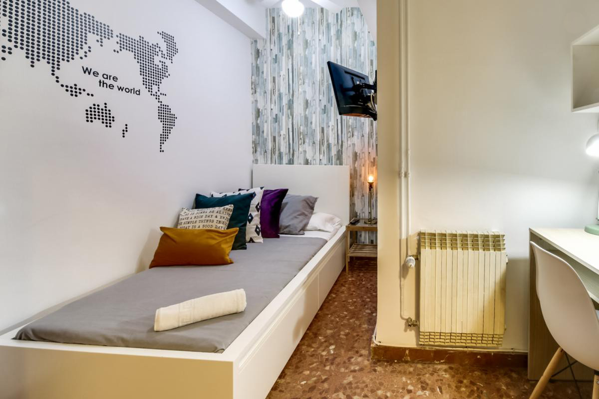 Compact room with TV and single bed in a residence with service